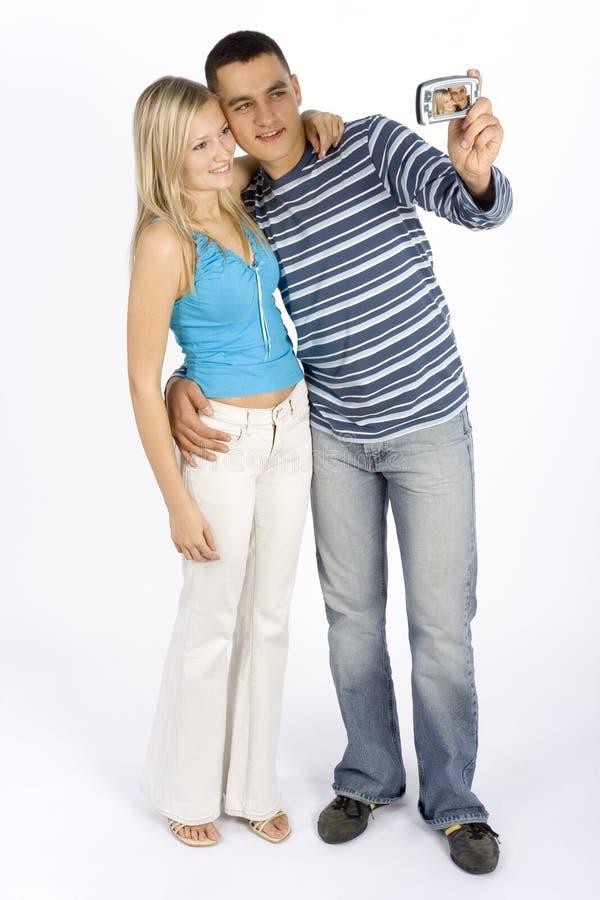 Giovani coppie che catturano maschera dal telefono/palmtop fotografia stock