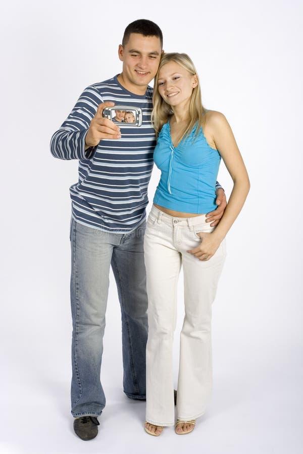 Giovani coppie che catturano maschera dal telefono/palmtop immagini stock