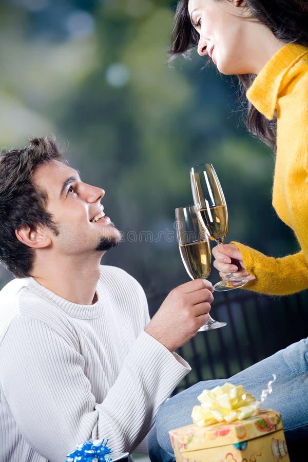 Giovani coppie che celebrano evento con i vetri ed i regali del champagne