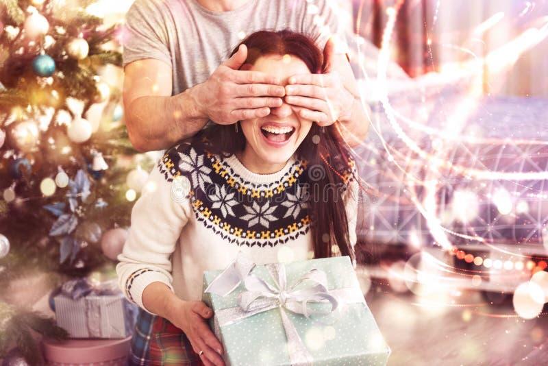 Giovani coppie che celebrano natale Un uomo ha presentato improvvisamente un presente alla sua moglie Il concetto di felicità del immagine stock libera da diritti