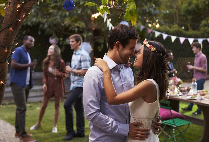 Giovani coppie che celebrano nozze con il partito in cortile immagini stock
