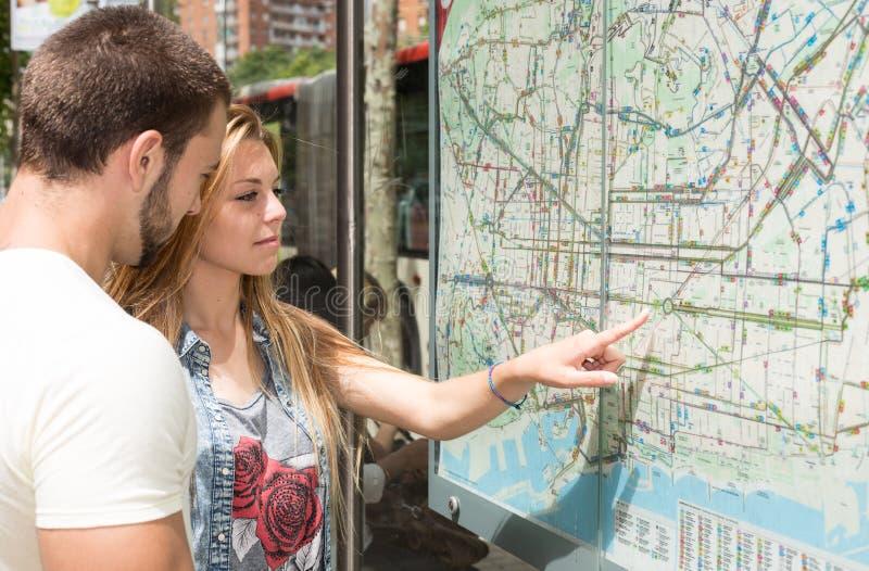 Giovani coppie che consultano una mappa fotografie stock