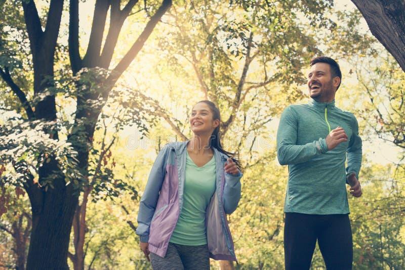 Giovani coppie che corrono insieme nel parco Esercitazione dei giovani fotografia stock libera da diritti