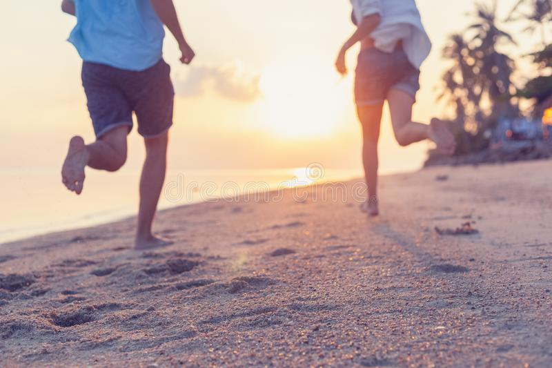 Giovani coppie che corrono lungo la spiaggia sabbiosa nei raggi del tramonto, fondo perfetto di immagine vaga per le agenzie di v immagini stock