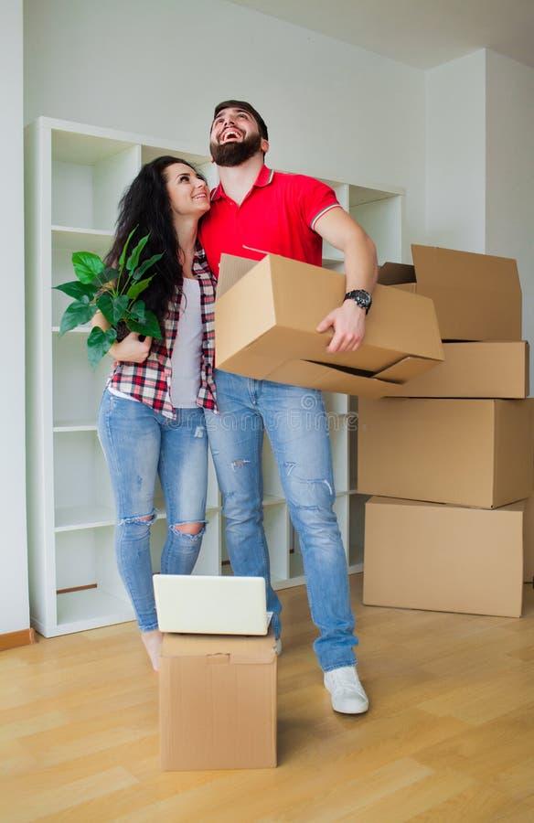 Giovani coppie che disimballano le scatole di cartone a nuova casa Casa commovente immagine stock