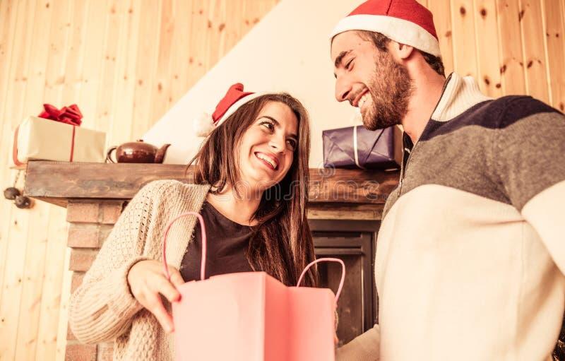 Giovani coppie che dividono i regali di Natale fotografie stock