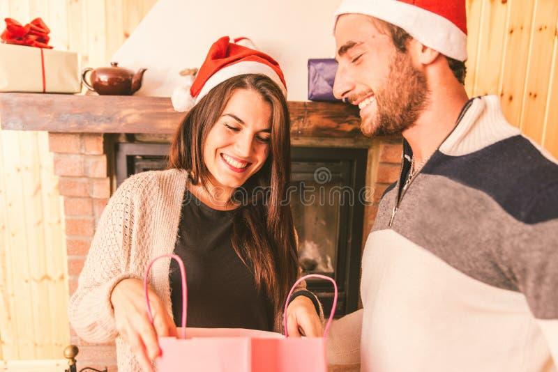 Giovani coppie che dividono i regali di Natale immagini stock libere da diritti