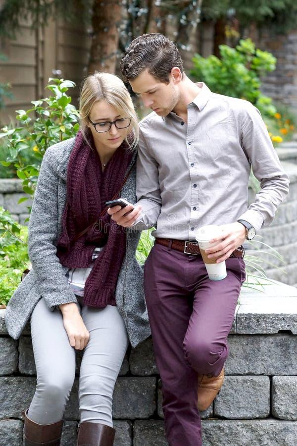 Giovani coppie che esaminano il loro Smartphone fotografia stock libera da diritti