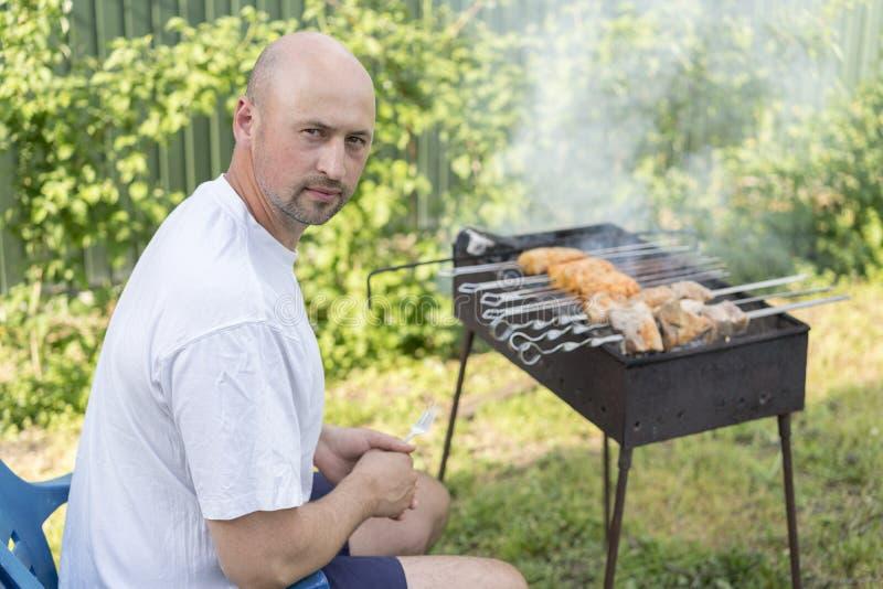 Giovani coppie che fanno barbecue nel loro giardino immagine stock