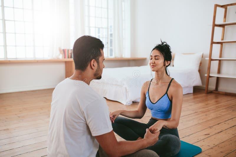 Giovani coppie che fanno insieme yoga a casa fotografia stock