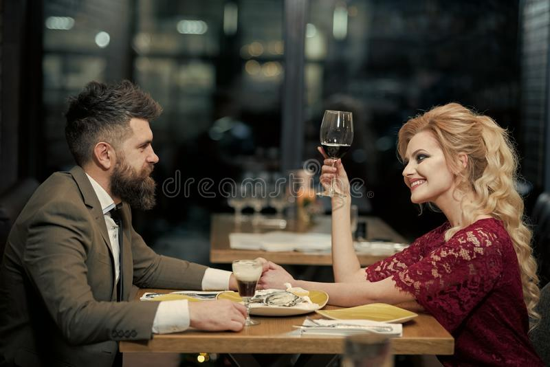 Giovani coppie che flirtano in caffè con le ostriche ed il vino immagine stock