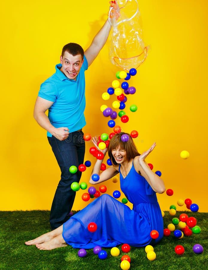 Giovani coppie che giocano con le palle colorate immagini stock