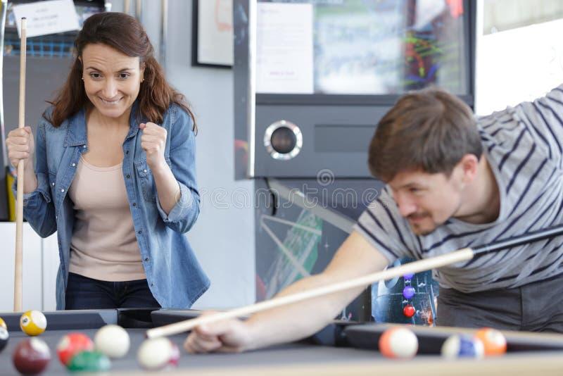 Giovani coppie che giocano insieme snooker nella barra fotografia stock libera da diritti