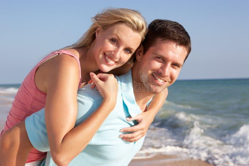 Giovani coppie che godono della festa della spiaggia al sole fotografie stock libere da diritti