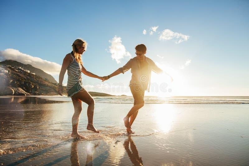 Giovani coppie che godono delle feste sulla riva di mare immagini stock