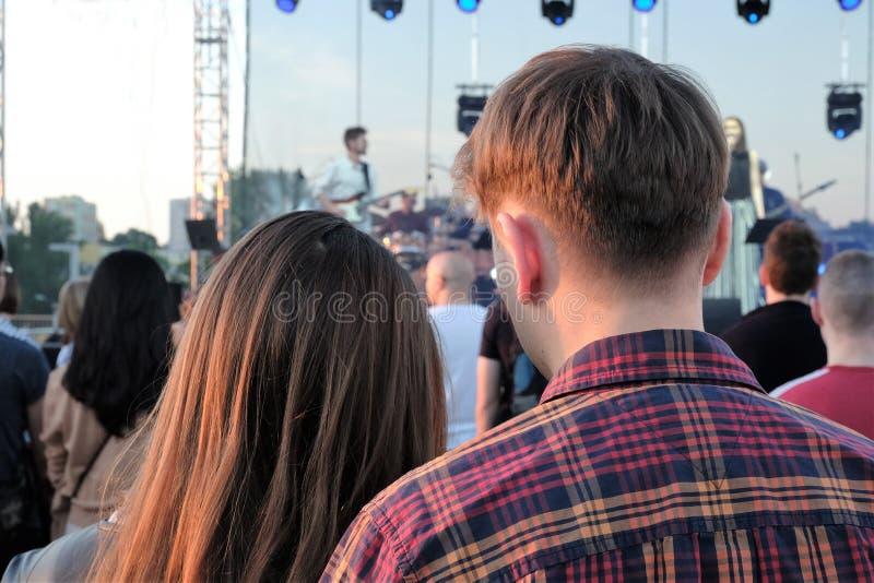 Giovani coppie che godono di un concerto su una sera soleggiata di estate immagini stock libere da diritti