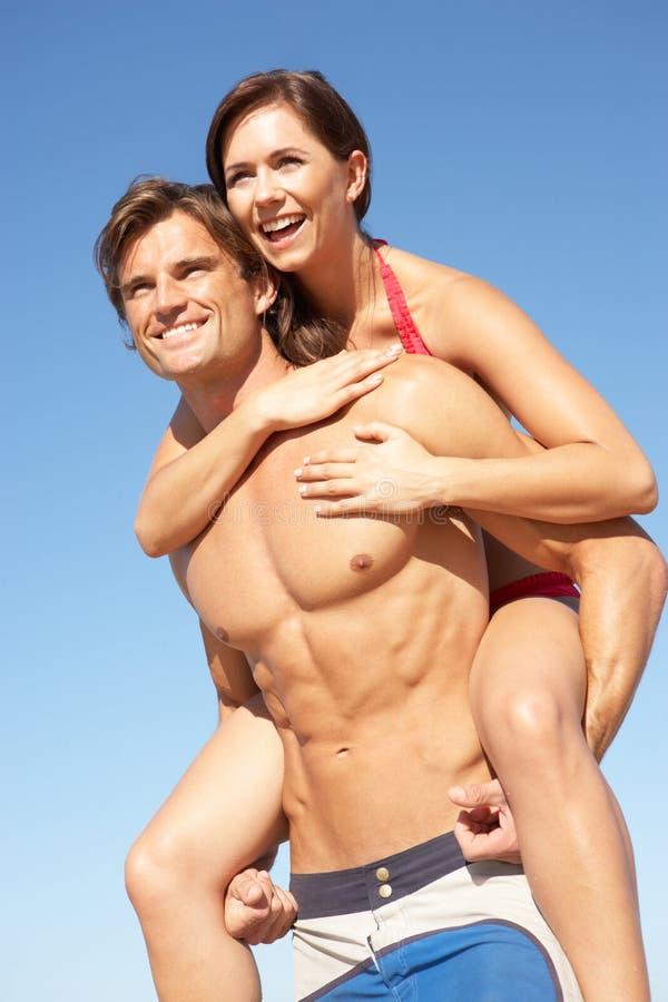 Giovani coppie che godono sulle spalle sulla festa della spiaggia fotografia stock