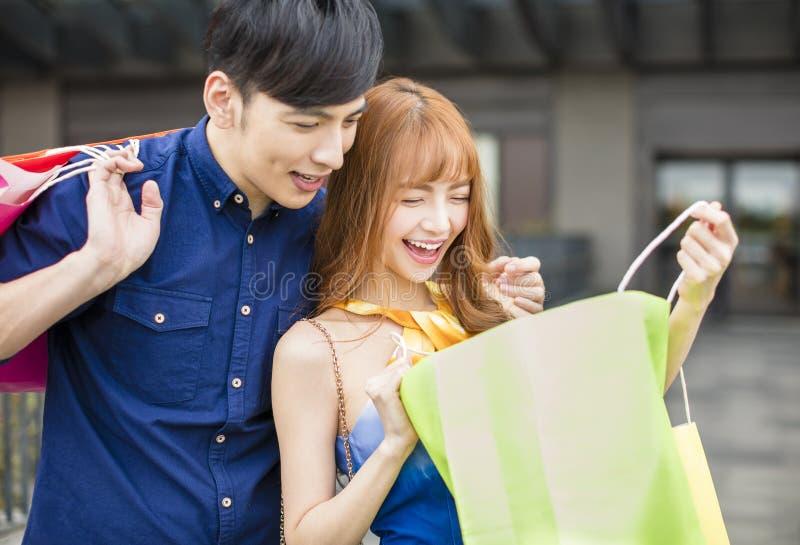 Giovani coppie che guardano il sacchetto della spesa fotografia stock