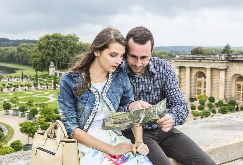 Giovani coppie che guardano in una mappa fotografia stock libera da diritti