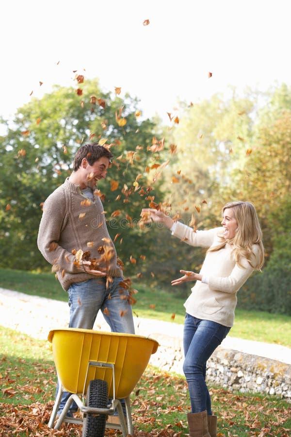 Giovani coppie che hanno divertimento con i fogli di autunno fotografia stock libera da diritti