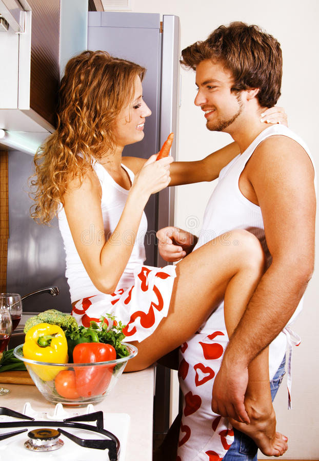 Giovani coppie che hanno divertimento nella cucina fotografie stock