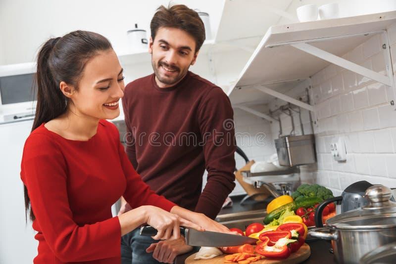 Giovani coppie che hanno uguagliare romantico a casa nelle verdure di taglio della donna della cucina fotografia stock libera da diritti