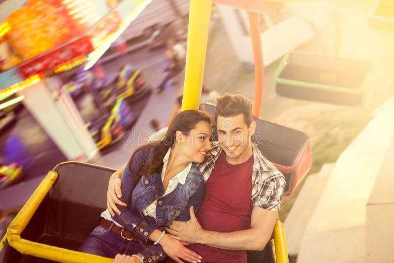 Giovani coppie che hanno un giro su una ruota di ferris fotografia stock libera da diritti
