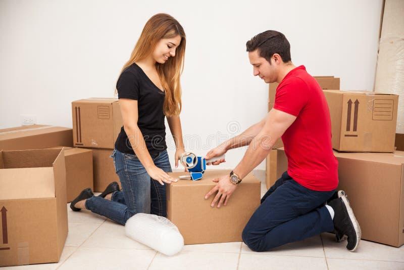 Giovani coppie che imballano alcune scatole fotografie stock
