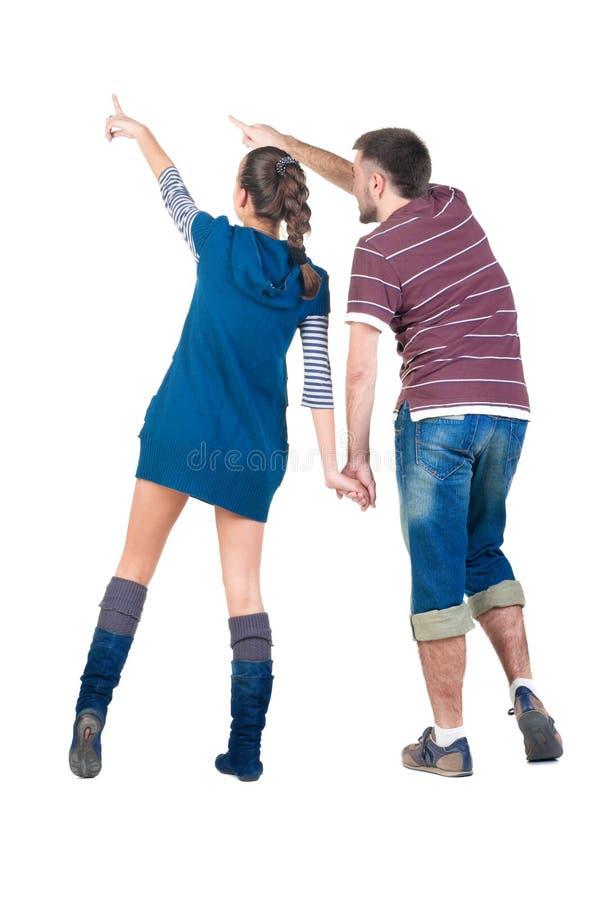 Giovani coppie che indicano alla parete bianca. fotografia stock