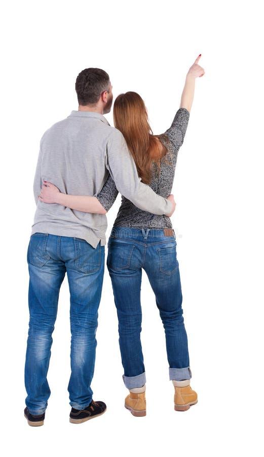 Giovani coppie che indicano alla vista posteriore wal (donna ed uomo) immagine stock