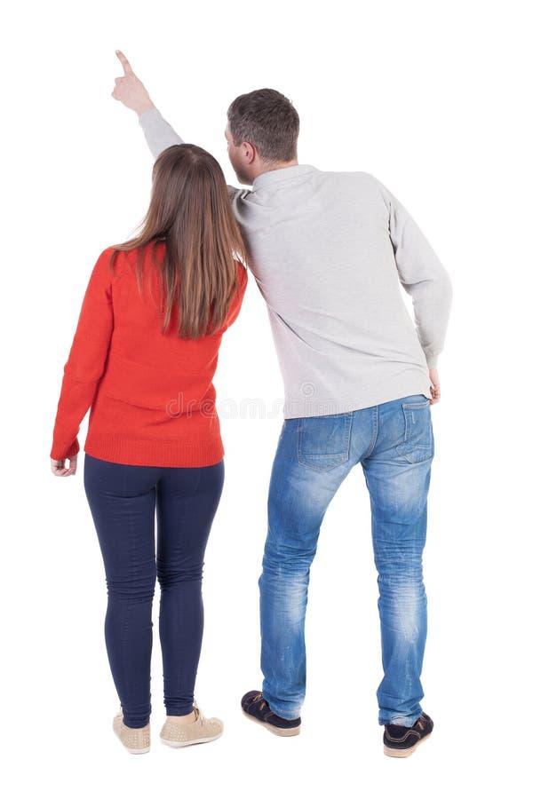 Giovani coppie che indicano alla vista posteriore wal (donna ed uomo) fotografie stock