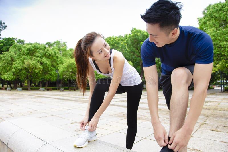 Giovani coppie che legano le scarpe da corsa e che si preparano per funzionare immagini stock libere da diritti