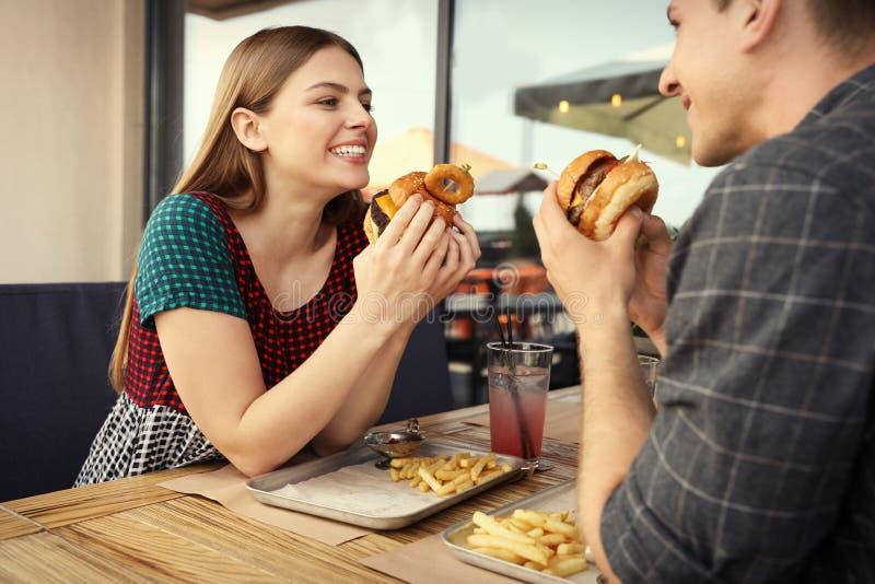 Giovani coppie che mangiano gli hamburger immagine stock