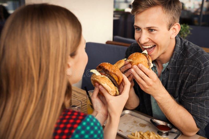 Giovani coppie che mangiano gli hamburger fotografia stock libera da diritti