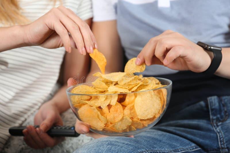 Giovani coppie che mangiano i chip mentre guardando TV fotografia stock