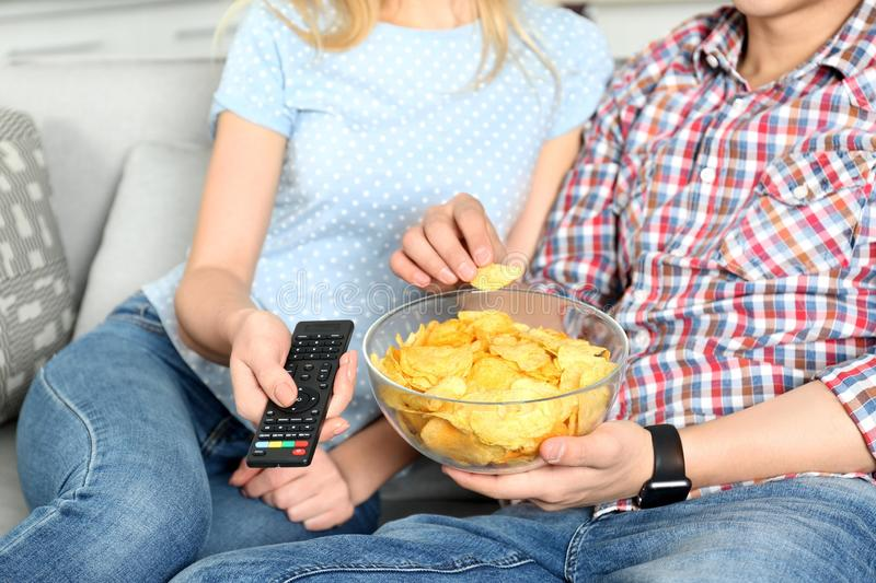 Giovani coppie che mangiano i chip mentre guardando TV fotografie stock