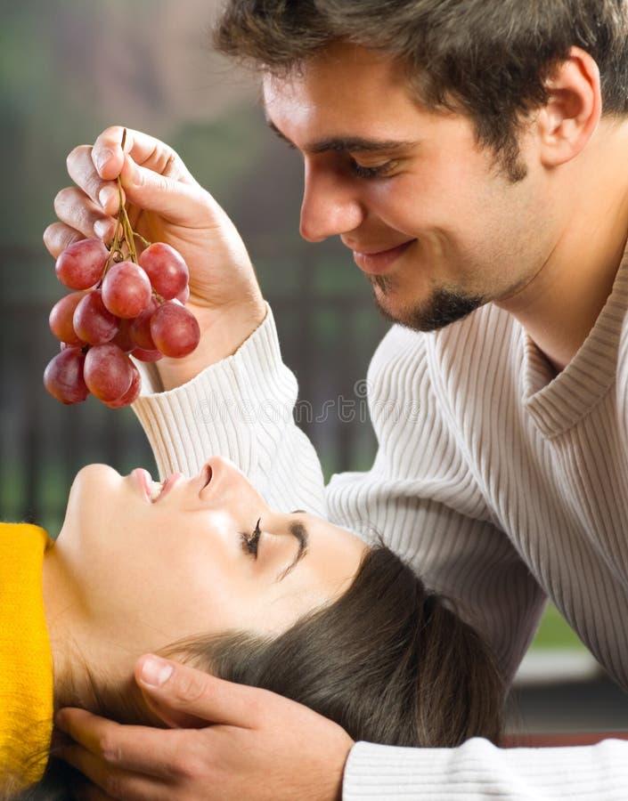 Giovani coppie che mangiano l'uva fotografia stock