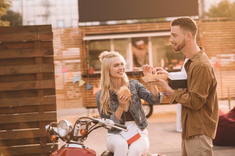 giovani coppie che mangiano le patate fritte ed hamburger fotografia stock