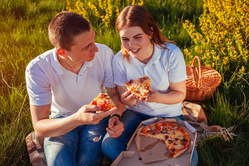 Giovani coppie che mangiano pizza e che chiacchierano fuori Donna ed uomo che hanno picnic al tramonto lifestyle immagine stock libera da diritti
