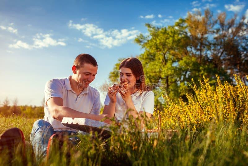 Giovani coppie che mangiano pizza e che chiacchierano fuori Donna ed uomo che hanno picnic al tramonto lifestyle fotografia stock