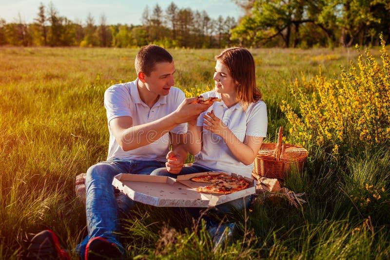 Giovani coppie che mangiano pizza fuori Donna ed uomo che hanno picnic al tramonto La gente che ha buon tempo fotografia stock libera da diritti