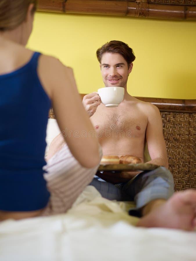 Giovani coppie che mangiano prima colazione sulla base immagine stock
