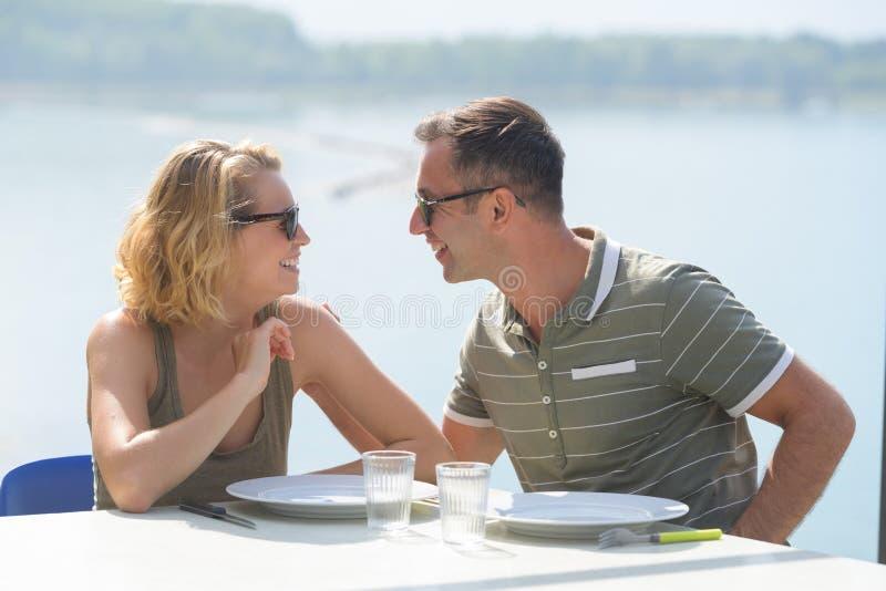 Giovani coppie che mangiano sul terrazzo del ristorante con la vista del lago immagini stock libere da diritti