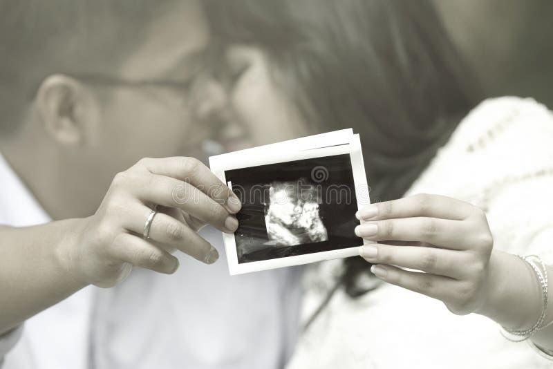 Giovani coppie che mostrano un sonogram fotografia stock libera da diritti