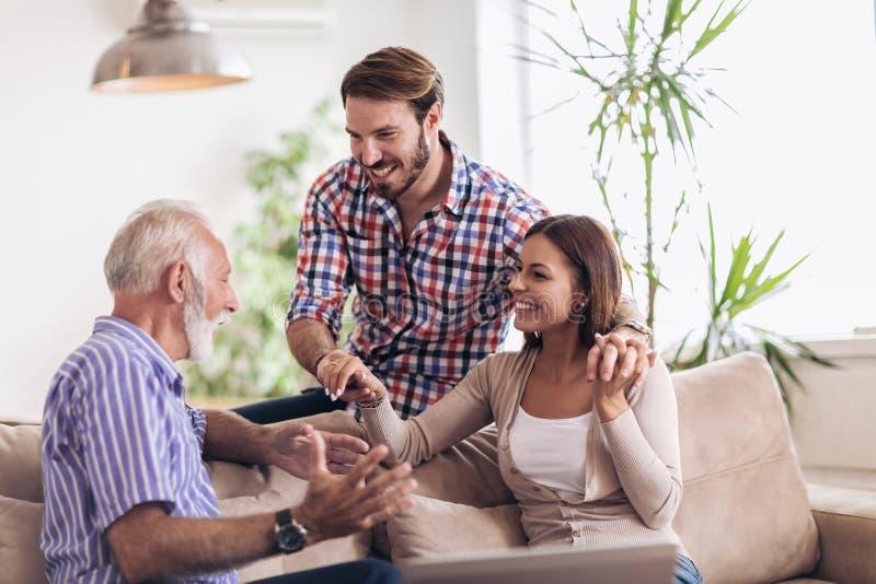 Giovani coppie che parlano con il loro padre senior fotografie stock