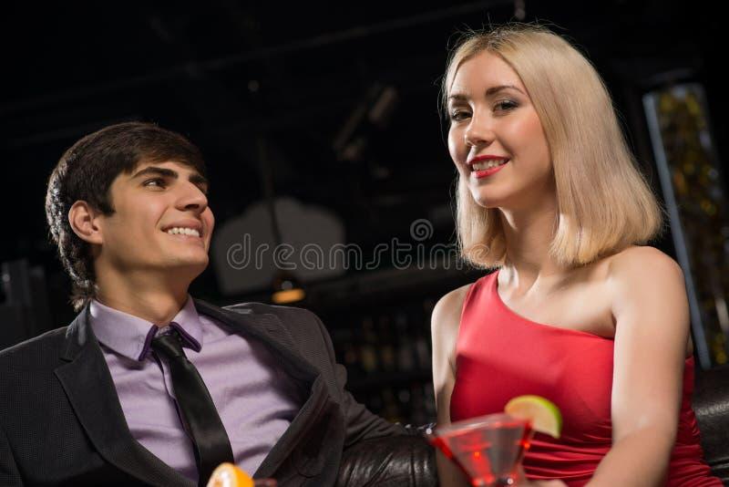 Giovani coppie che parlano in un night-club immagini stock
