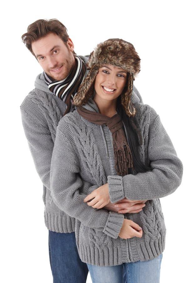 Giovani coppie che portano stesso sorridere del maglione immagini stock libere da diritti