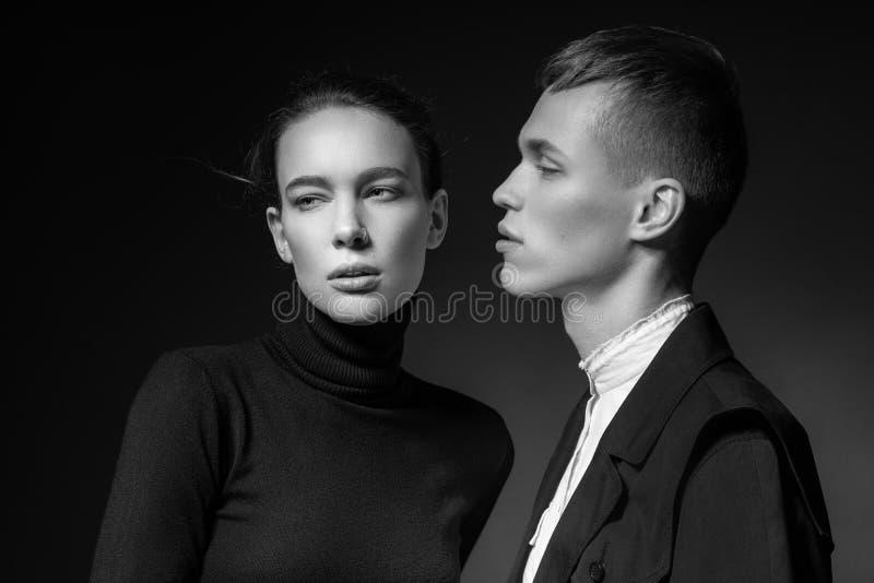 Giovani coppie che posano sul fondo scuro fotografia stock