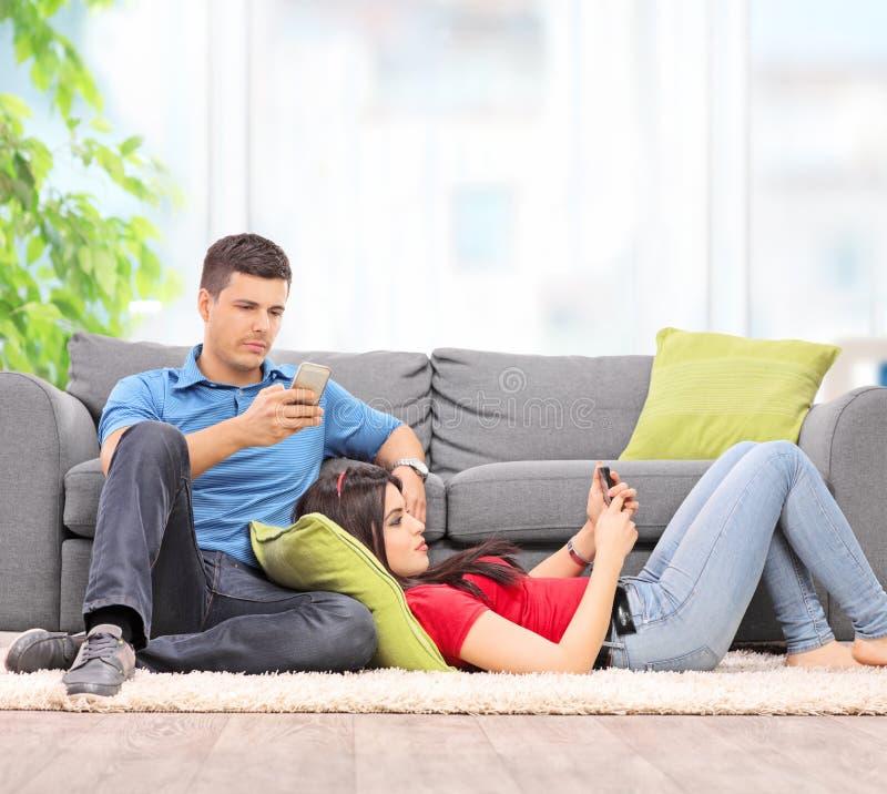 Giovani coppie che praticano il surfing sui loro telefoni cellulari da un sofà fotografia stock libera da diritti