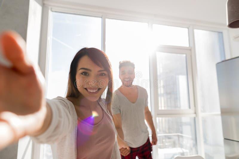 Giovani coppie che prendono la foto di Selfie che si tiene per mano nella cucina, uomo ispano principale della donna asiatica immagine stock